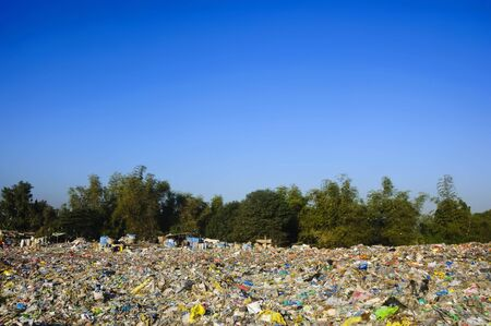 A sea of garbage starts to invade and destroy a beautiful countryside scenery; some poor people are also starting to make it their home where they can live and work. photo
