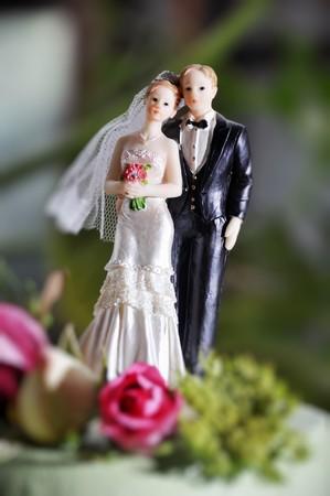Bride and groom figurines on wedding cake photo