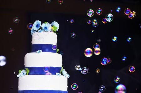 Layered wedding cake surrounded with floating soap bubbles Stock Photo