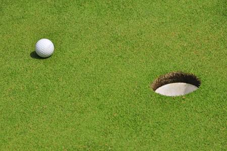 Close up of golf ball near a hole