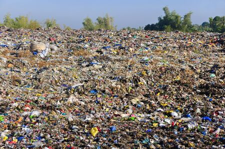 A sea of garbage starts to invade and destroy a beautiful countryside scenery  photo