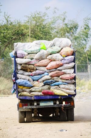 Garbage truck overflowing with trash in old sacks photo