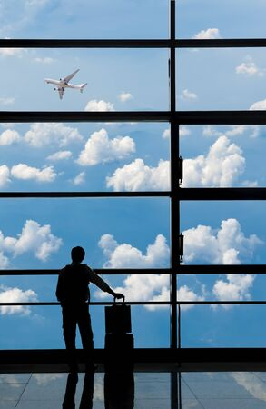 Businessman looks at airplane at airports departure area.