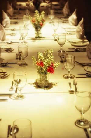 Close up of formal place setting. Focus red flowers at foreground