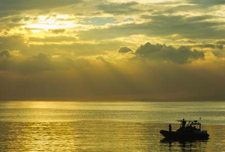 patrolling: Group of navy men patrolling Manila Bay at sunset, Philippines