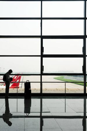 Shanghai, China - August 21, 2009: Adult male looks at LCD of his camera while waiting for his flight at Shanghai International Airport in China.