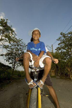 facing the camera: Smiling boy on bike facing camera