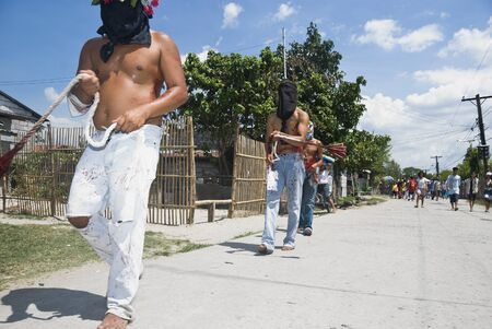 penitence: After an experienced volunteer scores his back with shards of glass embedded on a wooden block, a Filipino flagellant scourges himself with a rope tipped with small wooden sticks designed to hit the small wounds on his back.  He walks around town barefoot Editorial