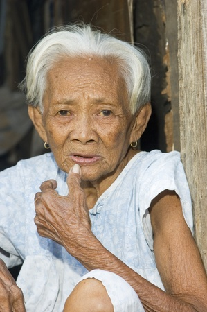 PHILIPPINES - APRIL 21:  Unidentified old Filipino woman looks blankly at camera on April 21, 2006 in a slum area in Manila, Philippines.  She is one of the thousands of poor people in the Philippines. Stock Photo - 10003721