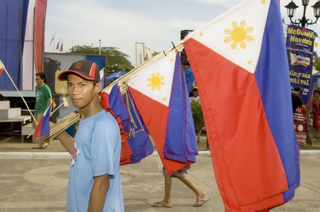 KAWIT, CAVITE, PHILIPPINES - JUNE 12: An unidentified young Filipino flag vendor sells small Philippine flags during the celebration of the countrys independence on June 12, 2006 in Kawit, Cavite.