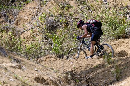 QUIRINO, PHILIPPINES - MARCH 29: Unidentified mountain biker pushes uphill on March 29, 2007 in Quirino, Philippines during a