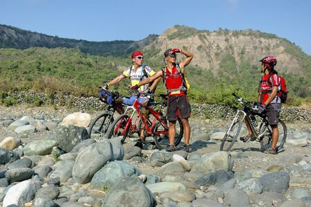 QUIRINO, PHILIPPINES - MARCH 31: Unidentified mountain bikers figure out their way across a dry river on March 31, 2007 in Quirino Province, Philippines during a  Stock Photo - 10003839