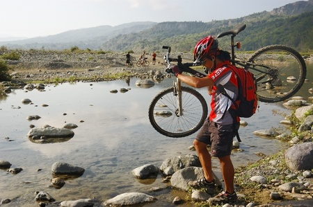 QUIRINO, PHILIPPINES - MARCH 31: Unidentified mountain biker carries his bike across a shallow part of a river on March 31, 2007 in Quirino, Philippines during a Bike for a Cause expedition.