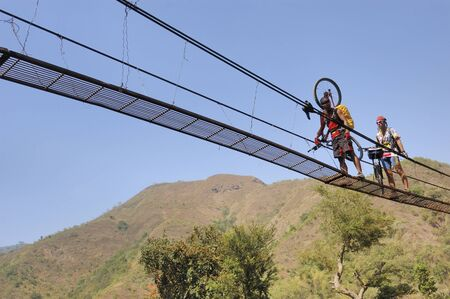 QUIRINO, PHILIPPINES - MARCH 31: Unidentified mountain bikers cross a foot bridge on March 31, 2007 in the mountains of Quirino, Philippines during a