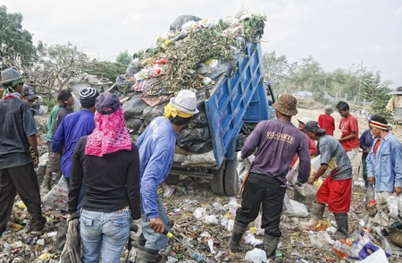 CAVITE, PHILIPPINESS. - FEBRUARY 12: Unidentified scavengers wait for truck to drop its load so they can rummage for recyclable items on February 12, 2010 in Cavite, Philippines.  Garbage disposal is a big problem in the Philippines.