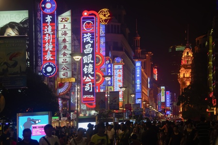 SHANGHAI - AUGUST 20, 2009: Nanjing Road on August 20, 2009 in Shanghai.  Thousands of foreign and local tourists stroll nightly under bright neon signs on Nanjing Road, Shanghai.