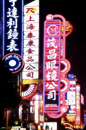 leisurely: SHANGHAI, AUGUST 20, 2009: Bright neon signs along Nanjing Road, Shanghai on August 20, 2009.  Bright neon signs greet thousands of tourists who flock to Nanjing Road nightly for a leisurely walk, shopping, or drink.