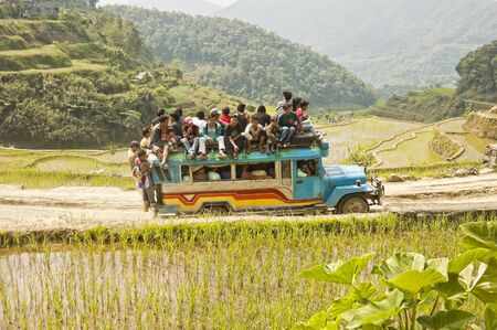 BANAUE, PHILIPPINES - APRIL 3: Unidentified men riding dangerously atop an assembled-from-junk jeepney in Banaue on April 3, 2007.