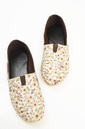 A pair of comfortable ladies slip-ons with floral patterns Stock Photo