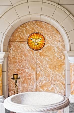 battesimo: Zona battesimale all'interno della chiesa cattolica con lo Spirito Santo e dell'acqua nel bacino