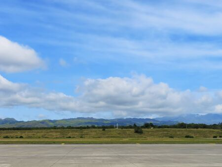 blue skies: Runway of small airport shot against a backdrop of mountains and blue sky Stock Photo