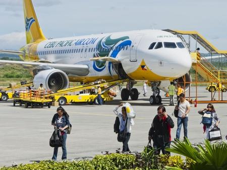 alight: Gensan, Filippine - 2 aprile 2011: Travelers scendere Cebu Pacific Air dopo lo sbarco in Gensan in una giornata molto calda, mentre il personale dell'aeroporto rimuovere il check-in bagagli dal piano.