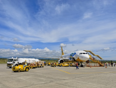 Gensan, Philippines - April 2, 2011: Passengers board a Cebu Pacific airplane bound for Manila, while airport ground personnel prepare the plane for the flight.