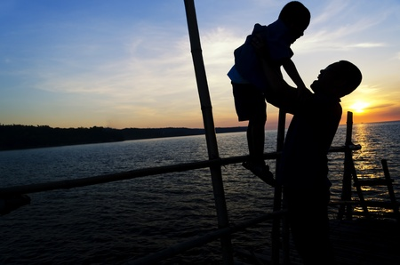 Silhouette of Asian father and son on a bamboo jetty during a bonding moment  Stock Photo