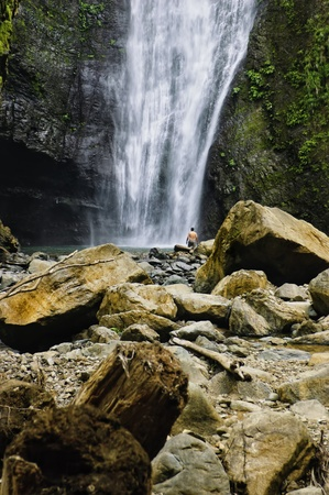 Man at the foot of a natural waterfall in a tropical forest in the Philippines Stock Photo - 13419110