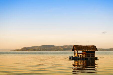 Raft with nipa hut in Taal Lake during sunrise Stock Photo