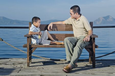 Father and son on wharf during a bonding moment  photo