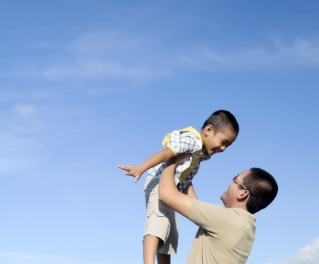 Father and son against blue sky during bonding moment Stock Photo