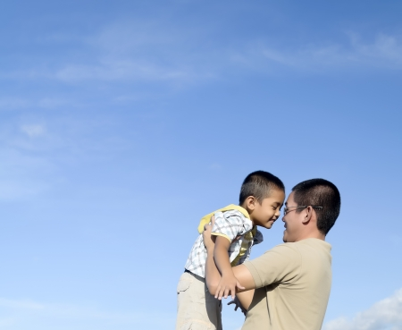 Father and son against blue sky during bonding moment