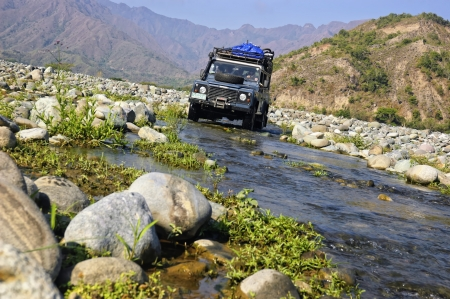 rugged terrain: A Land Rover Defender crosses a long, dry river in the province of Quirino, Philippines