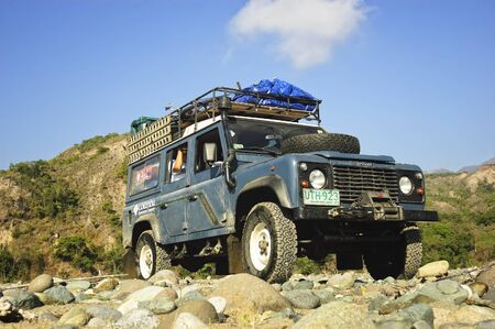 A Land Rover Defender crosses a long, dry river in the province of Quirino, Philippines