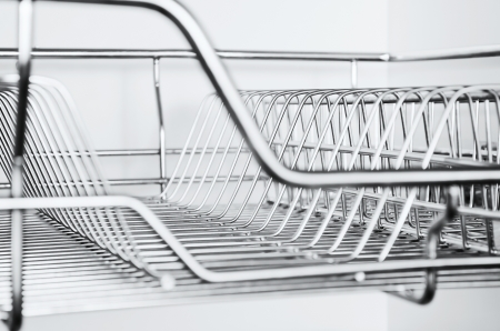 Close-up of stainless steel dish rack inside kitchen cabinet Stock Photo
