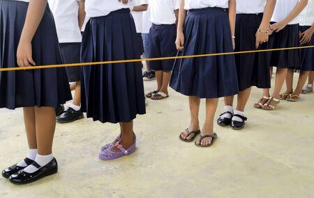 Students in school uniform standing in line inside an orange nylon cord
