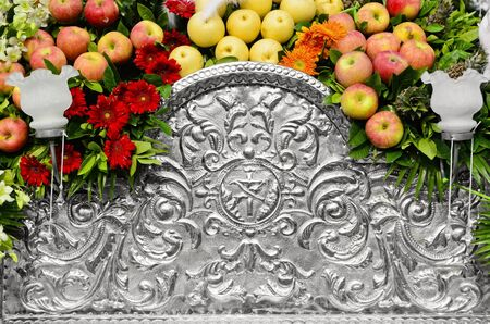 Detail of an old hammered aluminum religious art decorated with apples and flowers. photo