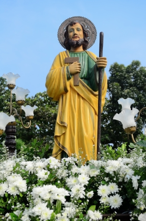 Statue of St. Joseph surrounded with flowers and lamps during a procession