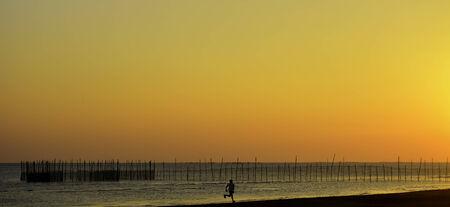 Runner over a fiery sunset beach photo