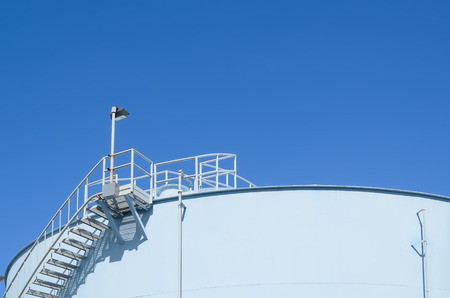 Blue industrial storage tank against cloudless blue sky Stock Photo