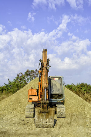 earth mover: Parked earth mover on top of gravel mound