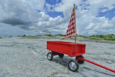 pull toy: A vintage red wagon toy in a sandy field Foto de archivo