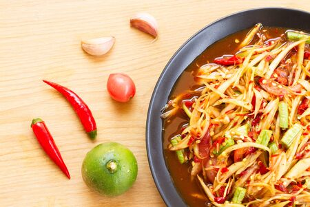 Som Tam or Spicy Papaya Salad In a black plate on a wooden table.