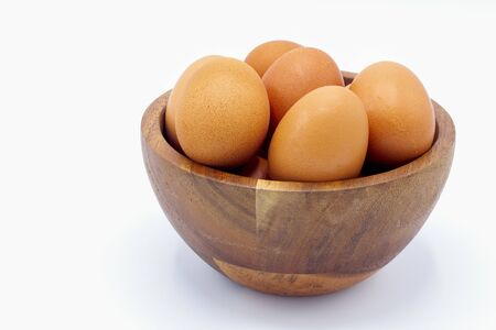 Fresh chicken eggs in a wooden bowl on a white background