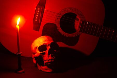 Human skull and guitar in candlelight on a wooden table