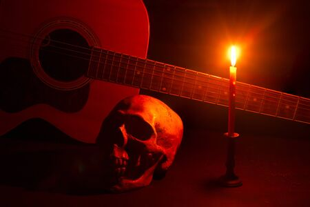 Human skull and guitar in candlelight on a wooden table Stock Photo - 133608864