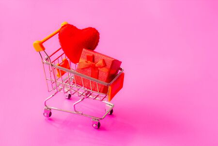 shopping cart full of gifts of different colors on a pink background, with a negative space Reklamní fotografie
