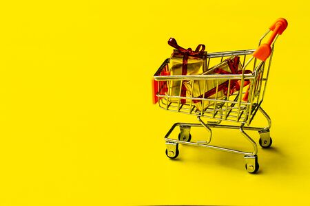shopping cart toy with on  yellow background.