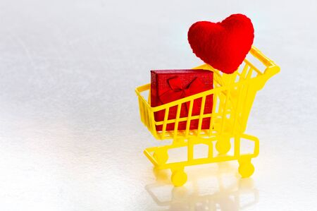 shopping cart with red present box and confetti red hearts on a gray background copy space Reklamní fotografie